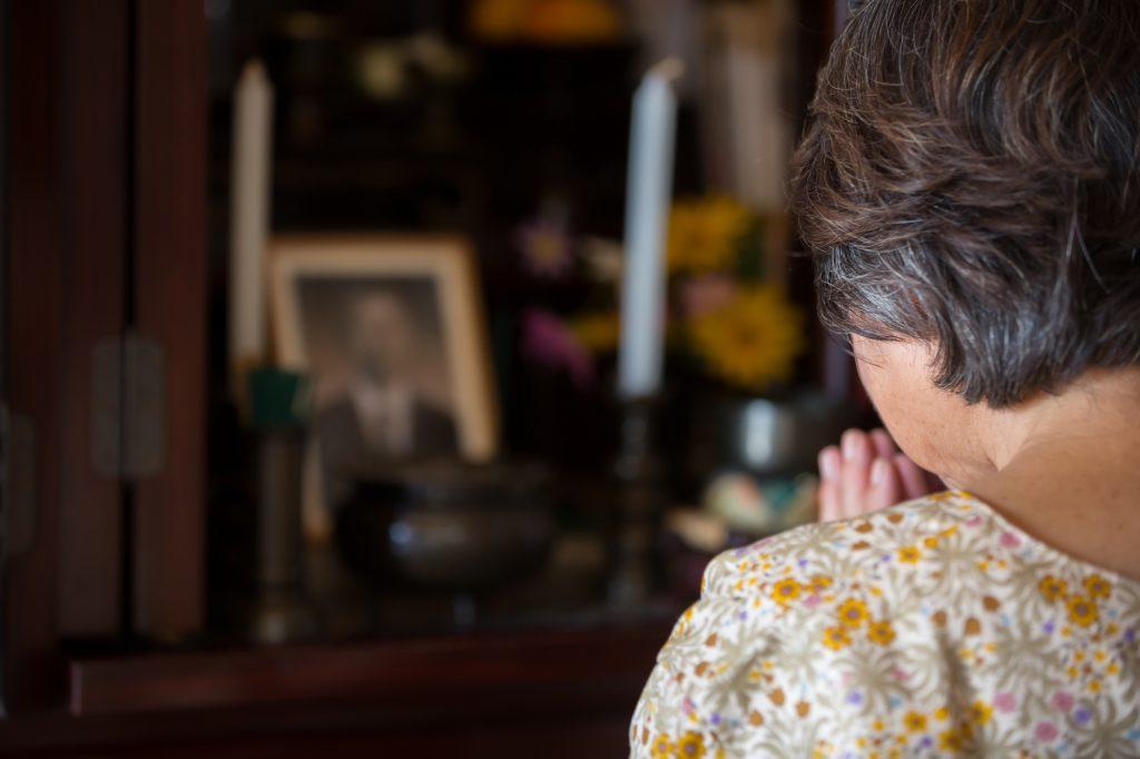 仏壇供養のタイミングでお祈りしてる女性