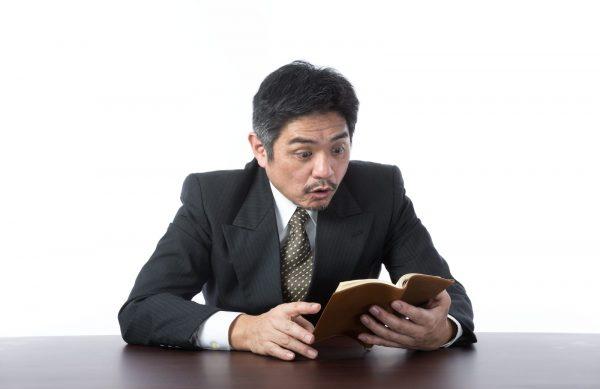 手帳を見て驚く男性