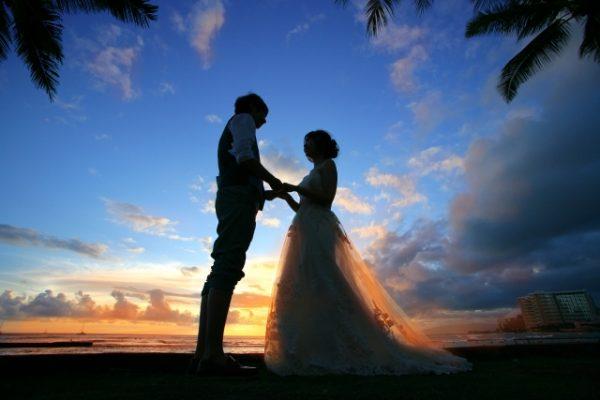 南国ビーチで結婚式の後撮りをする幸せいっぱいのカップル