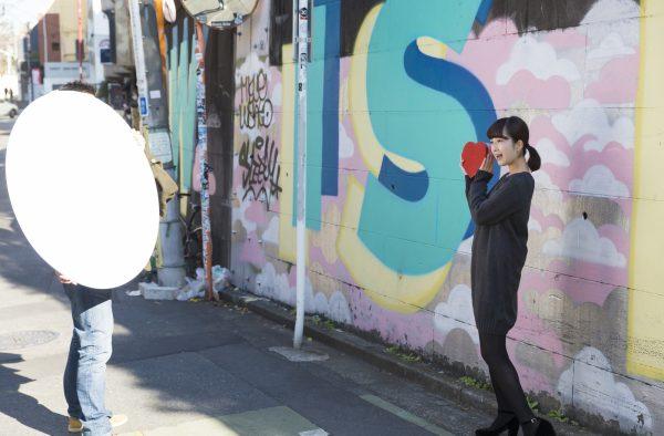 レフ板を使って撮影する女性