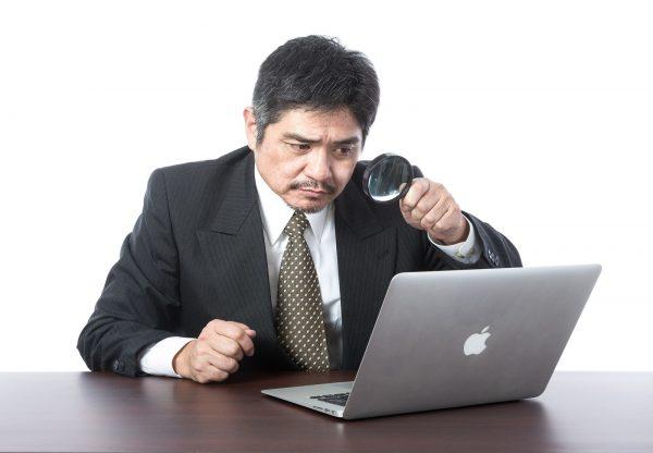 パソコンを虫眼鏡を使って見る男性