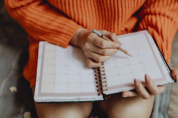 手帳を持つ女の子。税金の期間である起算日を記入中。