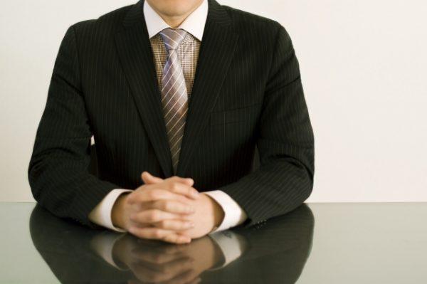 指を組むスーツの男性